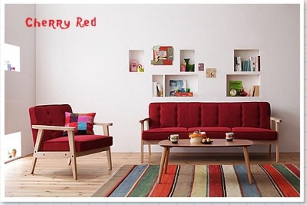 赤いソファとカラフルストライプのラグ