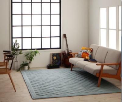 ブルーのラグとグレーのソファ