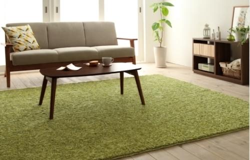 ベージュのソファとグリーンのラグ