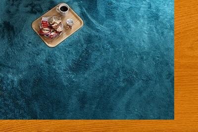 ミディアムブラウンの床とブルーのラグ